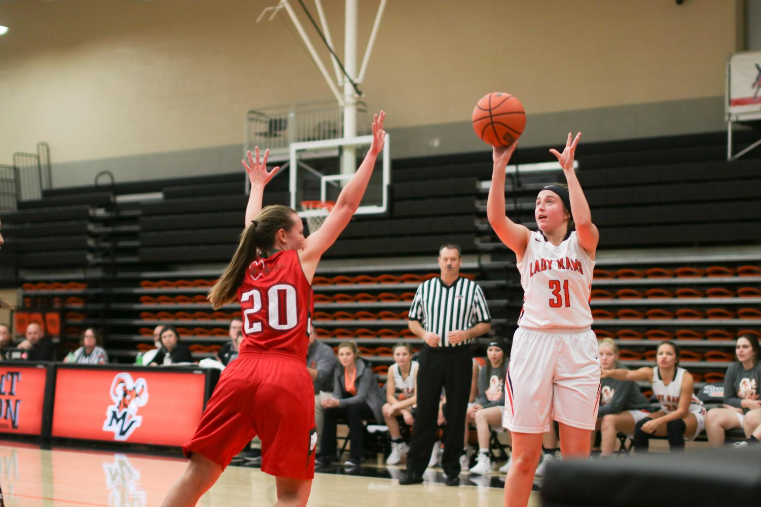 Olivia Ryan, 19 shoots a three-point shot while a Flaming Hearts defender attempts a block.